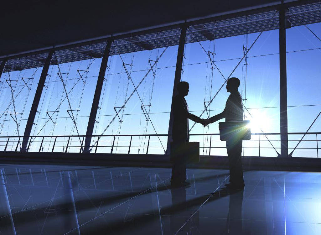 Two businessmen shaking hands in new office space.